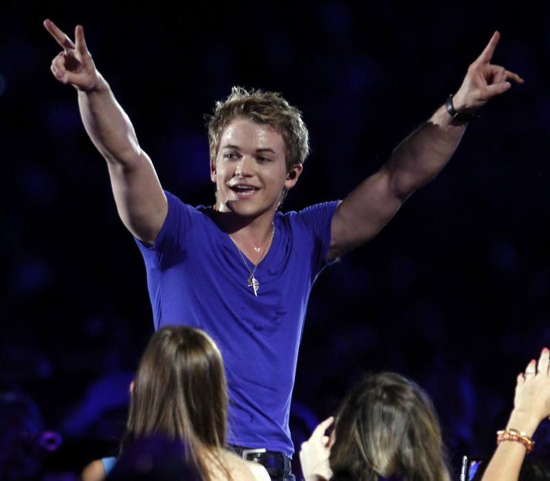 FILE - This June 9, 2012 file photo shows singer Hunter Hayes performs at the 2012 CMA Music Festival in Nashville, Tenn. Hayes knows a thing or two about hurricanes. The south Louisiana native has seen his share of storms. On Friday, Hayes, a 20-year-old from Breaux Bridge, La., is returning to his home state to perform at a benefit concert for a New Orleans area hospital Friday, and on Sunday, he'll be singing the national anthem for the New Orleans Saints regular season opening game against the Washington Redskins. (Photo by Wade Payne/Invision/AP, file)