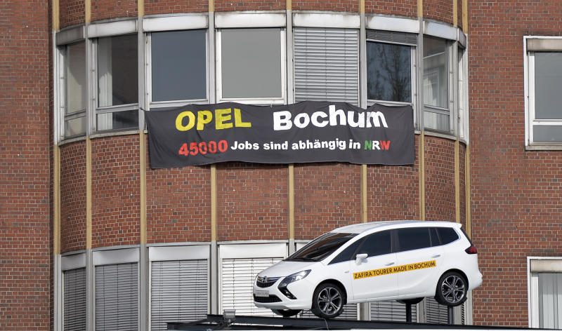 """A banner reading """"Opel Bochum - 45,000 jobs in North Rhine-Westphalia"""", hanging at the Opel car plant in Bochum, Germany, Wednesday, April 17, 2013.  General Motors' loss-making Opel division has confirmed it plans to end production at the plant in Germany by the end of 2014.   Adam Opel AG said Wednesday in a statement that the Bochum plant would wind down production as part of its plan to reduce costs and turn the division around. The plant's 3,200 workers make the Zafira compact. The plant's closure has been expected since workers there rejected a compromise restructuring that would have extended some production. (AP Photo/Martin Meissner)"""