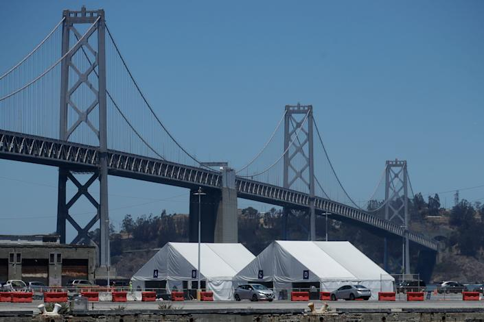 A COVID-19 testing site sits in front of the San Francisco-Oakland Bay Bridge during the coronavirus outbreak in San Francisco, Saturday, July 11, 2020.