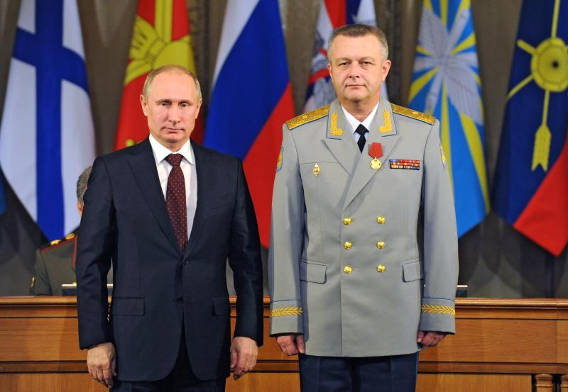 Russian President Vladimir Putin, left, presents a medal to Commander of the Russian Military Air and Space Defense Forces Alexander Golovko during a meeting with the top military brass in Moscow, Russia, Tuesday, Dec. 10, 2013. President Vladimir Putin has ordered Russia's armed forces to expand their presence in the Arctic region as part of efforts to revive the nation's military might. (AP Photo/RIA-Novosti, Mikhail Klimentyev, Presidential Press Service)