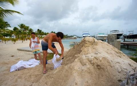 Employees of the Mercure Hotel fill sand bags on the Baie Nettle beach in Marigot - Credit: LIONEL CHAMOISEAU/AFP