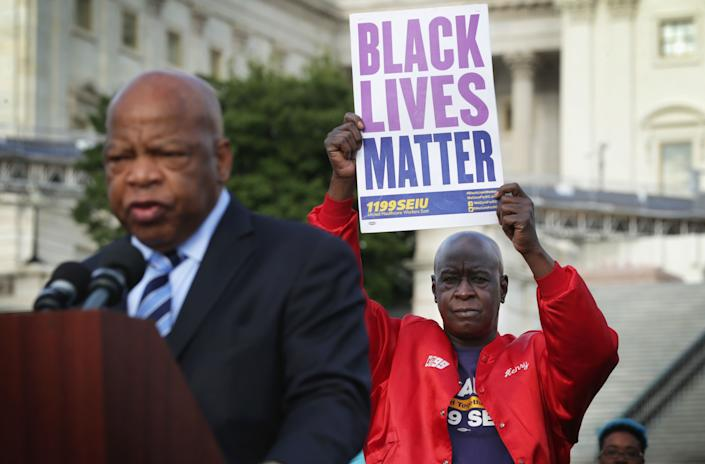 """Henry Singleton of New York City holds up a sign as U.S. Rep. John Lewis (D-Ga.) speaks during a rally to mark the finish of March2Justice on April 21, 2015, on the West Lawn of the U.S. Capitol in Washington, D.C. Dozens of marchers took part in an eight-day, 250-mile march from Staten Island, New York, to the nation's capital to demand congressional intervention to tackle """"the national crisis of police violence."""""""
