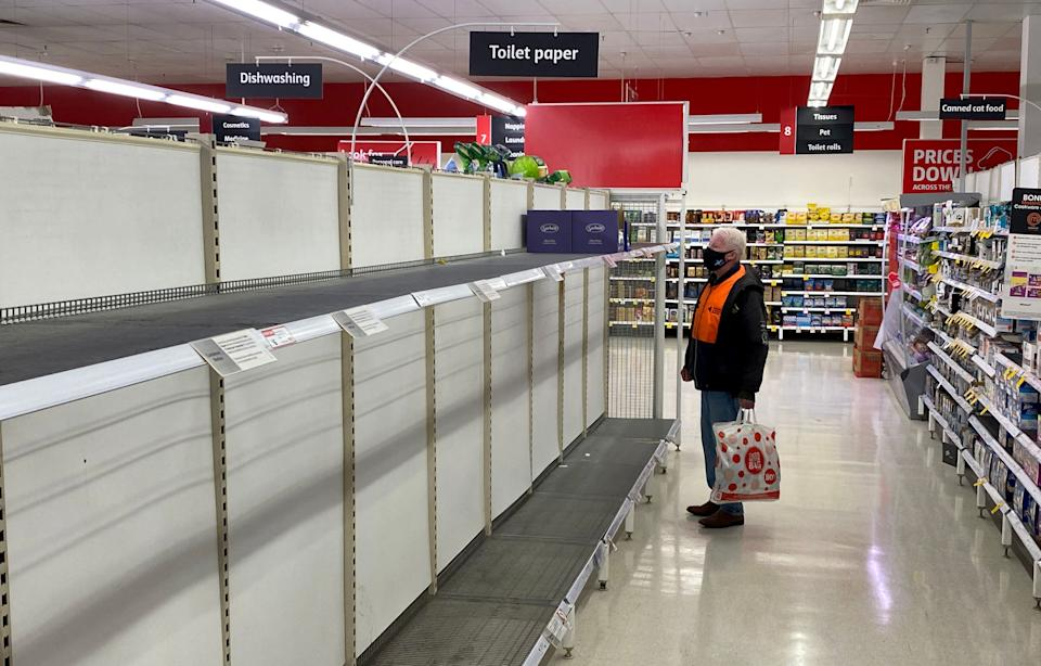A shopper looks at the empty toilet paper shelves in a Melbourne supermarket on Friday, the first of at least seven days of lockdown. Source: Getty
