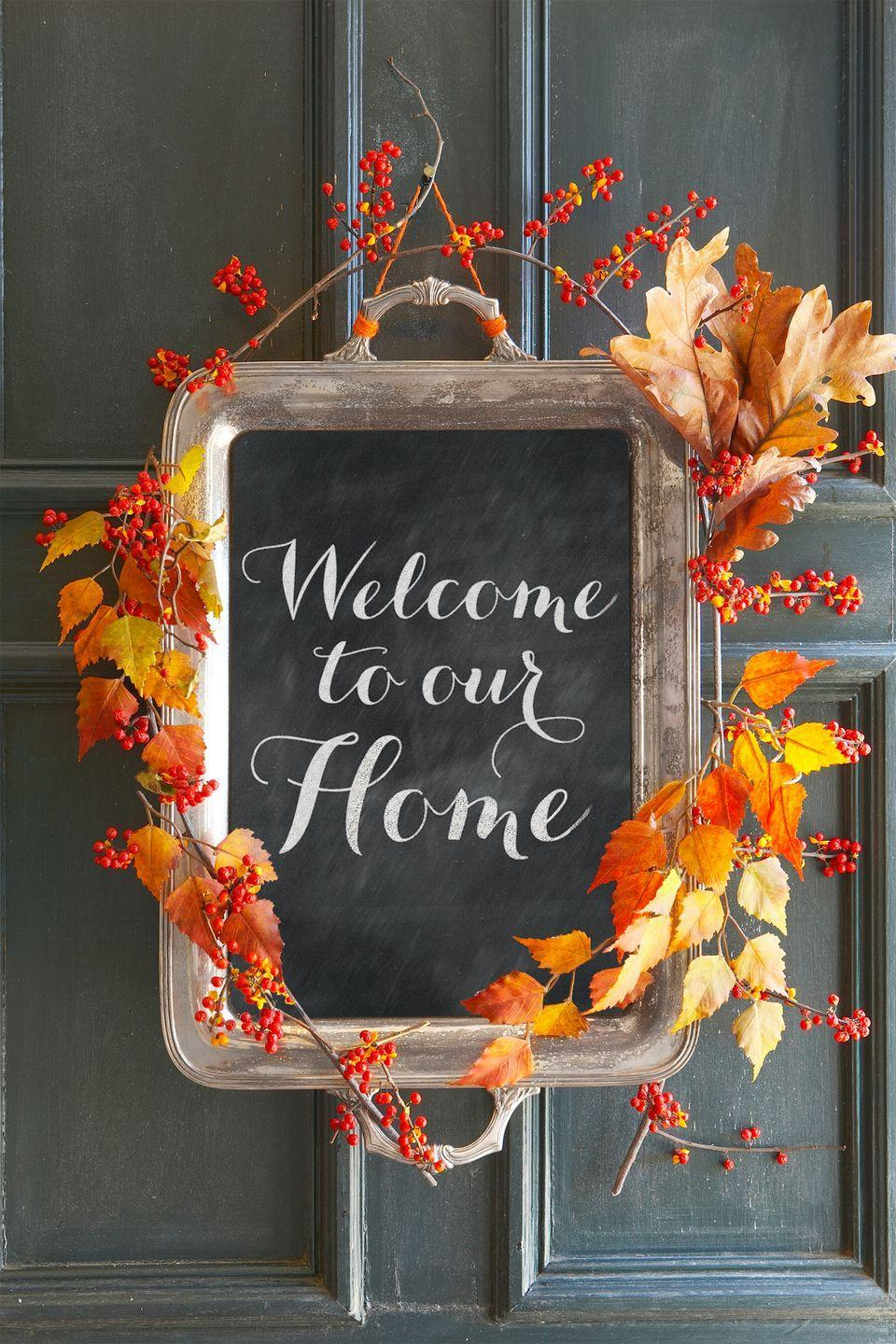 """<p>To make this welcome sign, apply a layer of <span class=""""redactor-unlink"""">chalkboard paint</span> to the inside of an old tray. Autumn branches and bittersweet berries add the perfect finishing touch. Pro tip: Swap out the foliage to make the sign work all year long.</p>"""