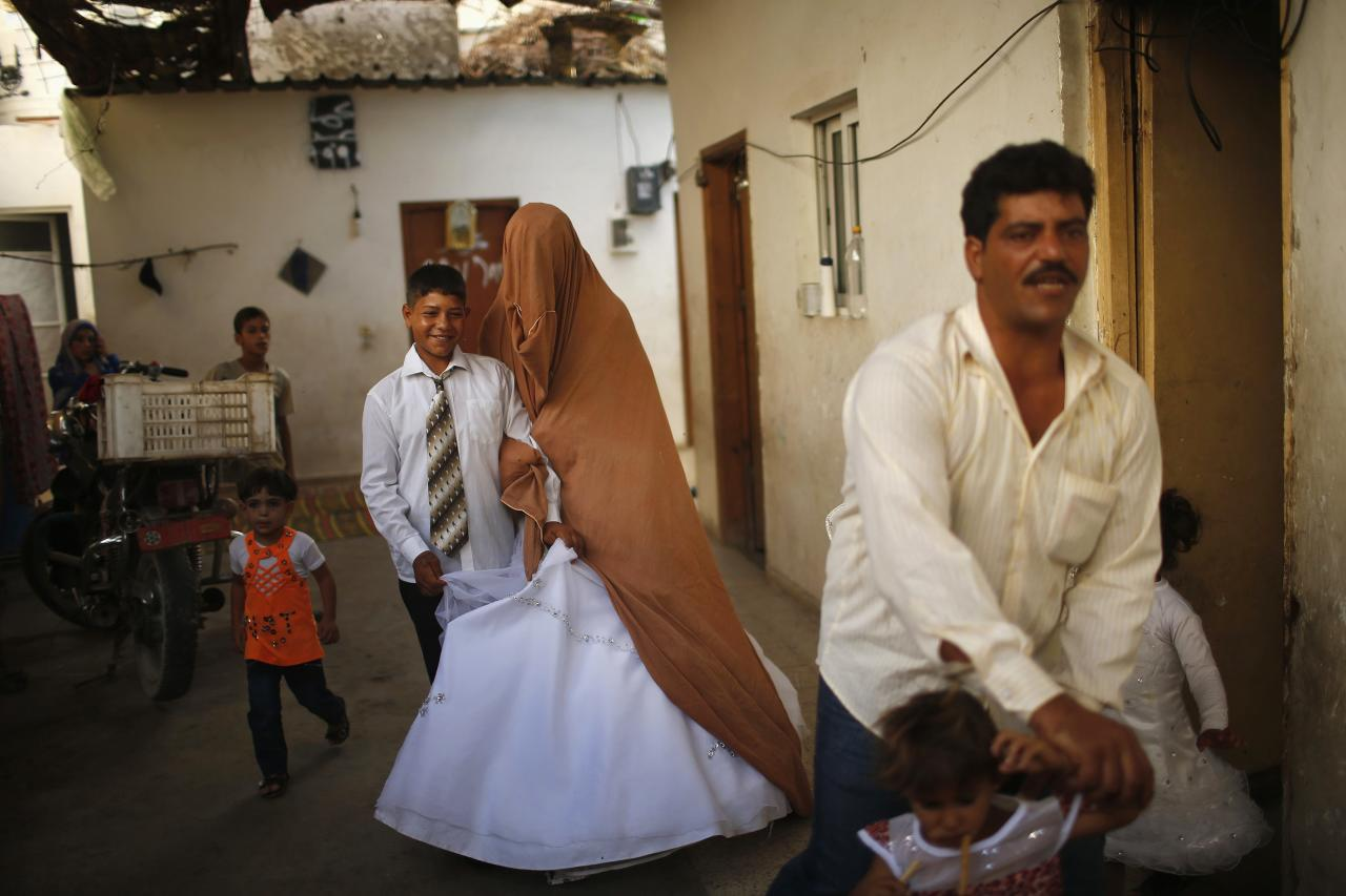Young Palestinian bride Tala Soboh (2nd L), 14, and her groom Ahmed, 15 leave Tala's house, which was damaged during an Israeli strike in 2009, during their wedding party in the town of Beit Lahiya, near the border between Israeli and northern Gaza Strip September 24, 2013. REUTERS/Mohammed Salem (GAZA - Tags: POLITICS CIVIL UNREST)