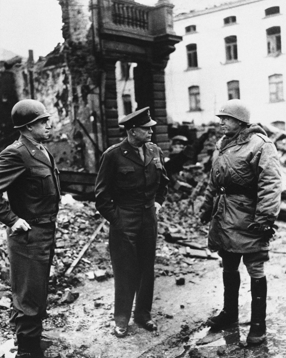 """FILE - In this Feb. 5, 1945, file photo, from left, Lt. Gen. Omar Bradley, commander, U.S. Twelfth Army Group; Supreme Allied Commander Dwight D. Eisenhower; and Gen. George S. Patton, commander, U.S. Third Army, survey the damage in Bastogne, Belgium. In 2020, the world marked the 75th anniversary of the end of World War II. Sterling Publishing, in cooperation with The Associated Press, released an illustrated book called """"Victory: World War II In Real Time,"""" filled with original AP dispatches from the time to mark the occasion and scores of original news photos. (AP Photo/File)"""