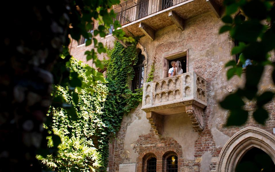 A couple kisses on the balcony of Juliet's House in Verona, overlooking the courtyard - Getty