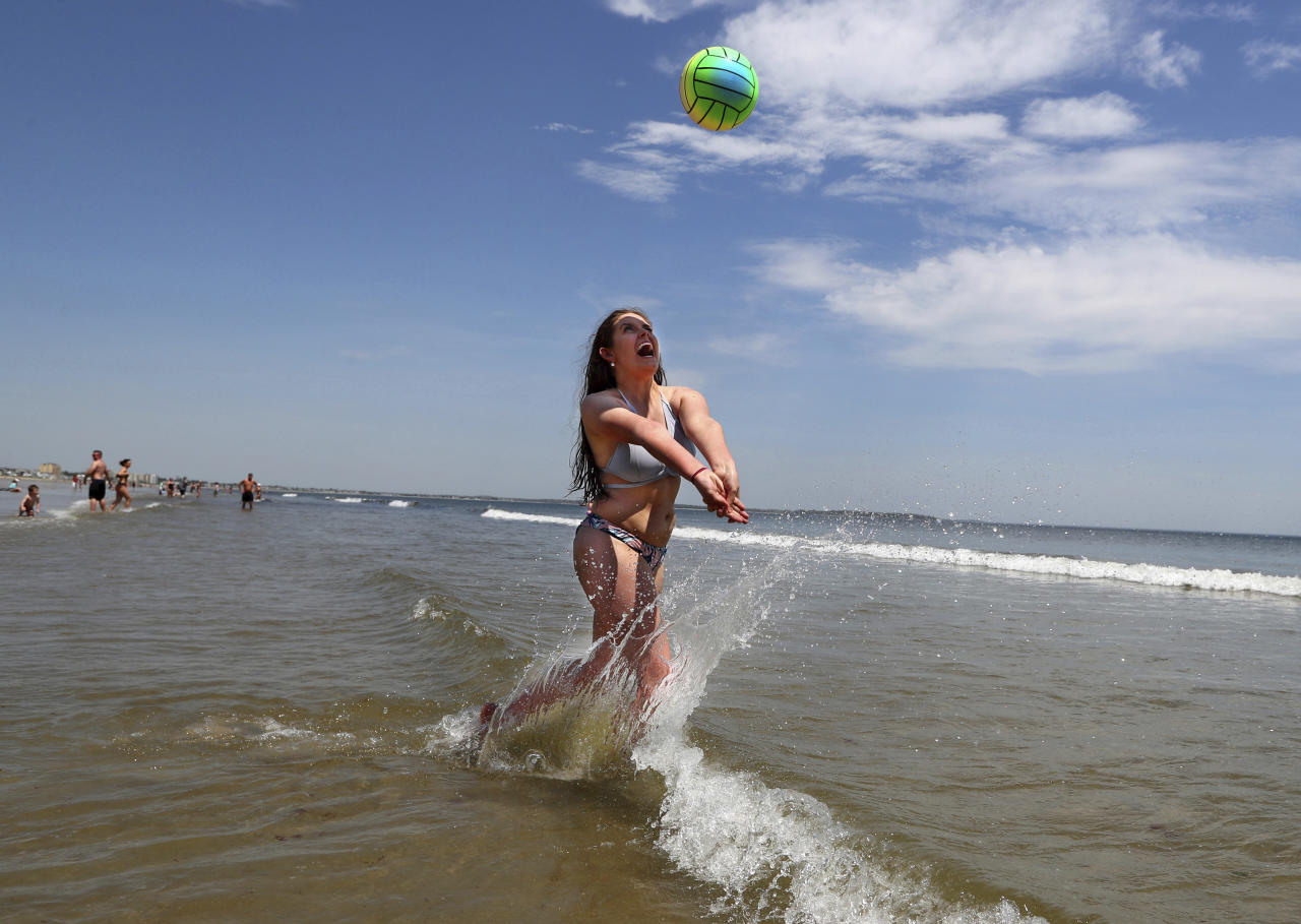 FILE - In this May, 18, 2017, file photo, Nessa King of Wyndham, Maine, returns a shot while playing volleyball in record breaking heat at Old Orchard Beach, Maine. As a summer vacation destination, Maine has something for everyone, from hiking and beaches to adventure and the arts. (AP Photo/Robert F. Bukaty, File)