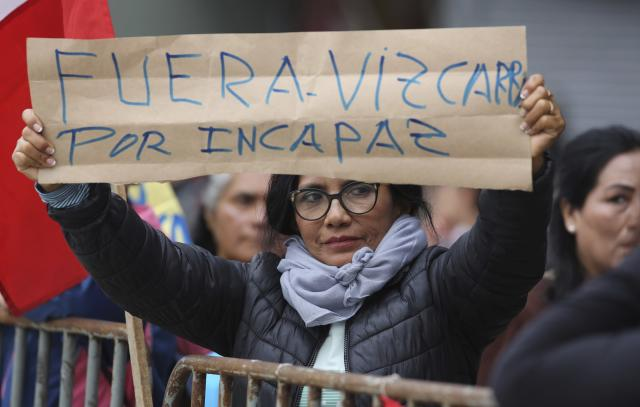 "A woman holds up a sign with a message that reads in Spanish; ""Get out Vizcarra, you are incompetent"" during a protest outside Congress, in Lima, Peru, Monday, Sept. 30, 2019. The political duel between Peruvian President Martin Vizcarra and Congress intensified in recent weeks after lawmakers decided to shelve Vizcarra's proposal to hold early presidential and congressional elections, which he argues is necessary to break the deadlock and stabilize the nation. (AP Photo/Martin Mejia)"