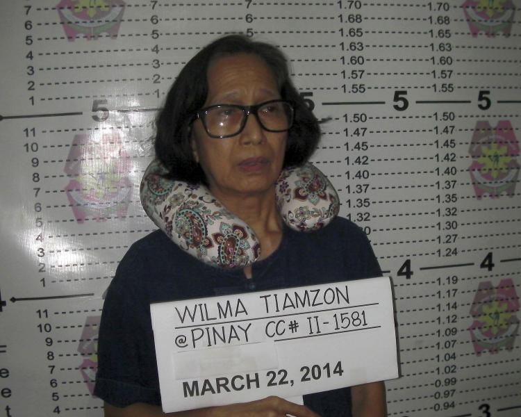 In this Saturday, March 22, 2014 photo released by the Philippine National Police Public Information Office, suspected communist leader, Wilma Austria Tiamzon, has her mugshot taken in Cebu province, central Philippines. Philippine officials said Sunday that they would not release two leaders of a violent rebel group fighting to overthrow the government, whose arrests were a serious blow to one of Asia's longest-running communist insurgencies. (AP Photo/Philippine National Police, Public Information Office)