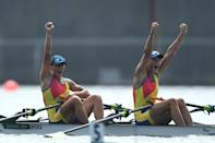 <p>Team Romania's Ancuta Bodnar and Simona Radis raise their hands in victory after winning the gold for Women's Double Sculls at Sea Forest Waterway on July 28.</p>