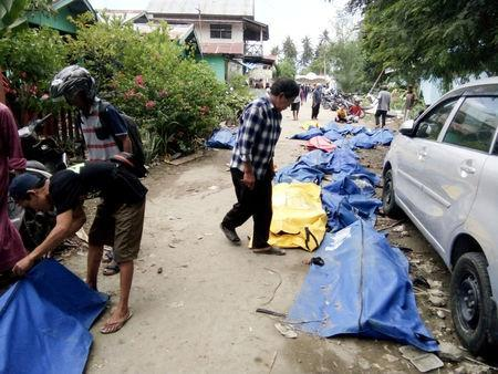 Residents check dead bodies to find their family at a street after earthquake hit in Palu, Indonesia September 29, 2018. REUTERS/Stringer