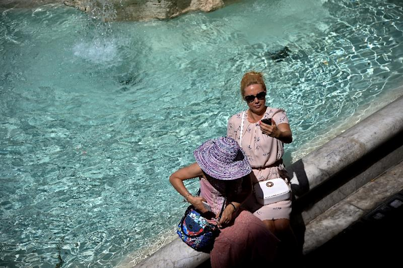 Tourists takes selfies by the Trevi Fountain in Rome