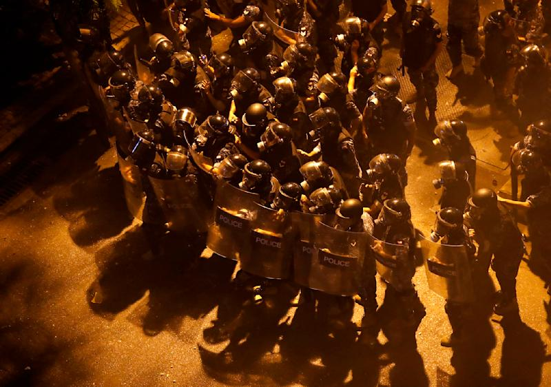 CORRECTS DATE TO EARLY FRIDAY, JUNE 12 Riot police advance to push back the anti-government protesters from a square near the government house, during a protest against the political leadership they blame for the economic and financial crisis, in downtown Beirut, Lebanon, early Friday, June 12, 2020. (AP Photo/Hussein Malla)