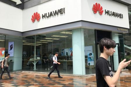 People walk past a Huawei store in Shenzhen
