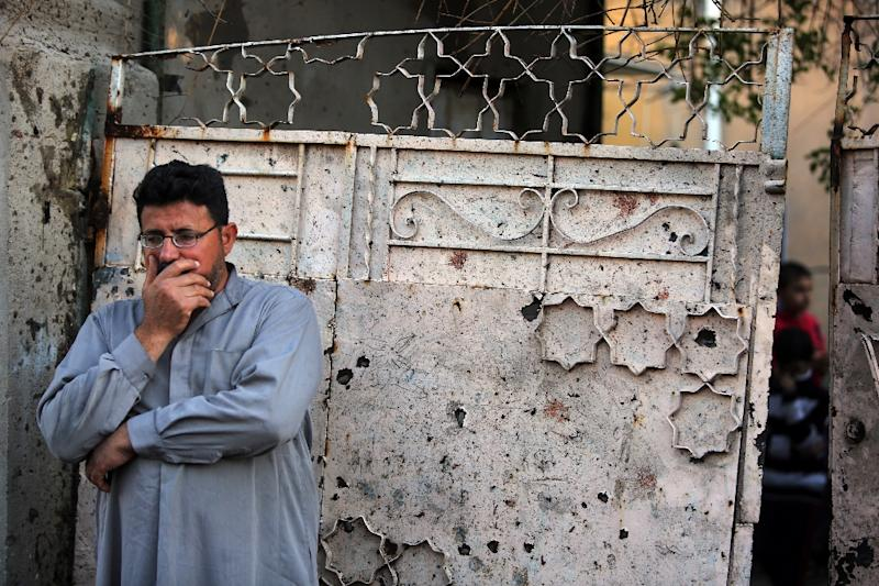 An Iraqi man stands in front of a door covered with shrapnel and blood stains after a suicide bomber reportedly blew himself up in the midst of a Shiite funeral ceremony in Baghdad on November 13, 2015