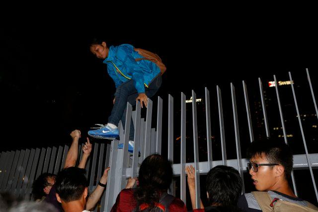 """A protester climbs over a fence as she leaves after hundreds stormed into a restricted area at the government headquarters, after a rally ahead of the October 1 """"Occupy Central"""" civil disobedience movement in Hong Kong September 26, 2014."""