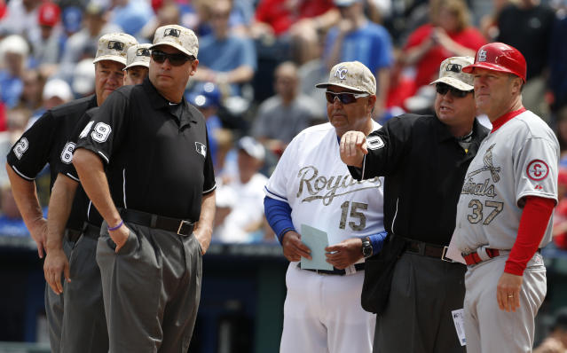 FILE - In this May 27, 2013, file photo, Kansas City Royals bench coach Chino Cadahia (15) and St. Louis Cardinals first base coach Chris Maloney (37) exchange line-ups with home plate umpire Rob Drake (30) before a baseball game at Kauffman Stadium in Kansas City, Mo. The exchange of lineup cards would be eliminated, fielders will be encourages to space themselves from baserunners between pitches and managers and coaches must wear masks while in the dugouts under Major League Baseball's proposed operations manual for starting the coronavirus-delayed season. (AP Photo/Orlin Wagner, File)