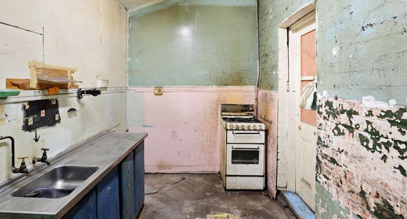 A rundown kitchen is pictured in a Waterloo home in Sydney.