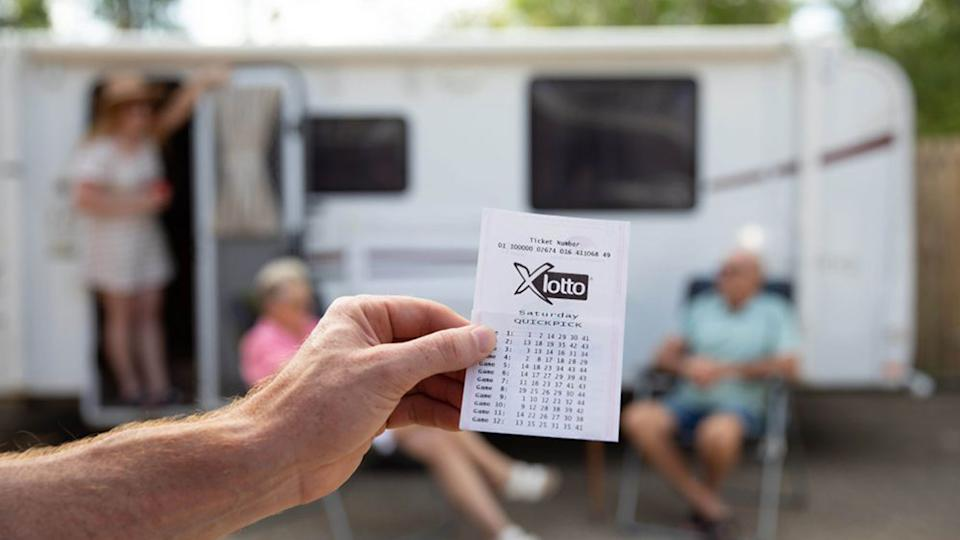 Pictured is someone holding up a XLotto lottery ticket in front of a caravan.