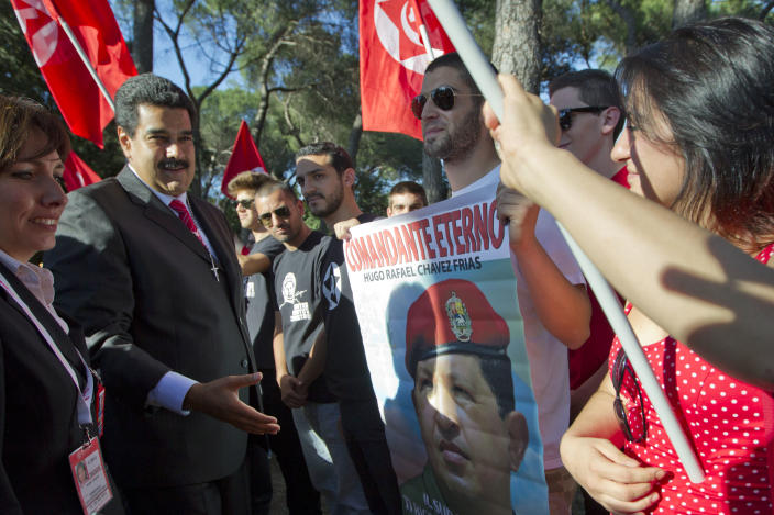 Venezuelan President Nicolas Maduro is greeted by far left-wing activists holding a photo of late Venezuelan President Hugo Chavez, as he arrives to make a press statement, in Rome, Sunday, June 16, 2013. Maduro is scheduled to meet Pope Francis Monday, June 17, during a private audience at the Vatican. (AP Photo/Andrew Medichini)