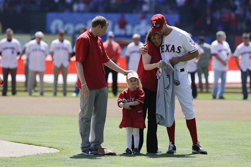 Robbie Parker, left, daughter Samantha, second from left, Parker's wife Alissa and Texas Rangers' David Murphy, gather on the field before Robbie threw out the ceremonial first pitch before a baseball game between the Los Angeles Angels and Texas Rangers Friday April 5, 2013, in Arlington, Texas. Parker, a North Texas native whose 6-year-old daughter, Emilie, was among the victims of the Sandy Hook school shooting in Connecticut, threw out the first pitch before the Rangers home opener, their favorite team. (AP Photo/Tony Gutierrez)