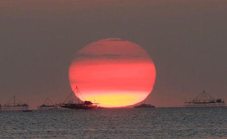 FILE PHOTO: Houses on stilts are seen as the sun sets around the Manila bay in Manila, Philippines February 5, 2015. REUTERS/Romeo Ranoco/File Photo