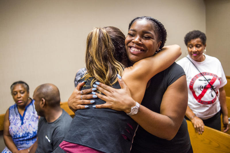 Flint resident Ariana Hawkins celebrates with Katrina Petri after Genesee District Judge David J. Goggins gave his decision during Nick Lyon's preliminary examination on Monday, Aug. 20, 2018 at Genesee District Court in Flint, Mich. Goggins ordered Lyons to stand trial for involuntary manslaughter in two deaths linked to Legionnaires' disease in the Flint area, the highest ranking official to stand trial as a result of the tainted water scandal. (Jake May/The Flint Journal via AP)