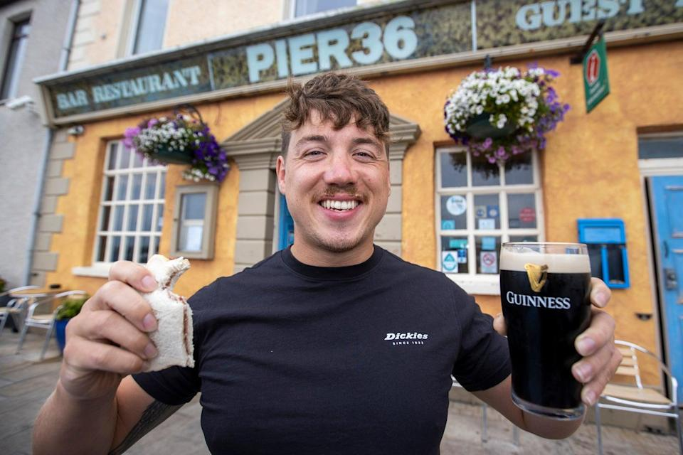 Jordan Leckey holding a celebrity jam sandwich and pint of Guinness outside Pier 36 at Donaghadee Harbour in Northern Ireland. Jordan set off on Monday swimming to Portpatrick in Scotland in the record time of nine hours and nine minutes. PA Photo. Picture date: Tuesday August 03 2021. See PA story ULSTER Swim. Photo credit should read: Liam McBurney/PA Wire