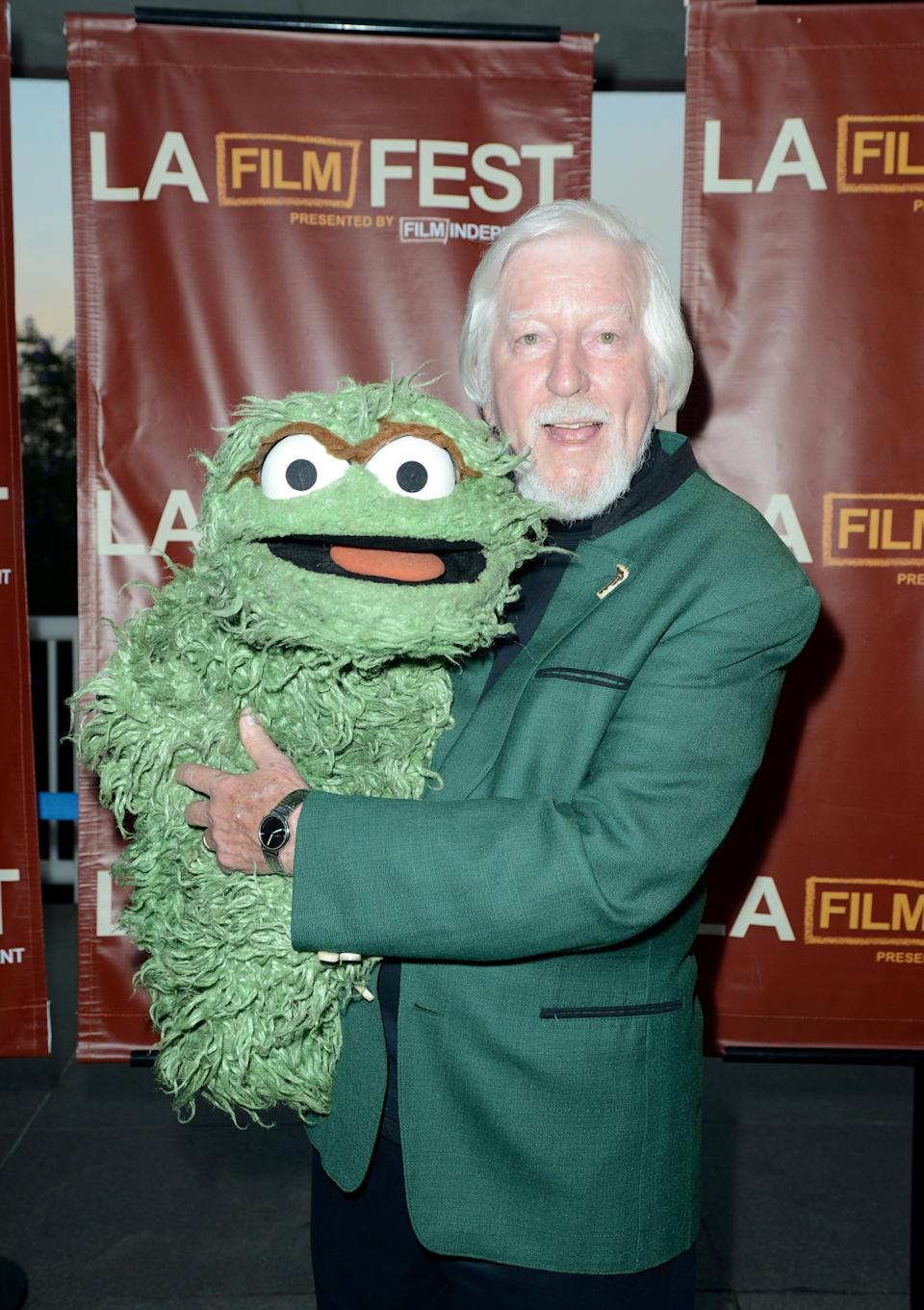 Spinney with Oscar the Grouch, another of his characters, at the 2014 premiere of the <em>I Am Big Bird </em>documentary, which told his story. (Photo: Getty Images)
