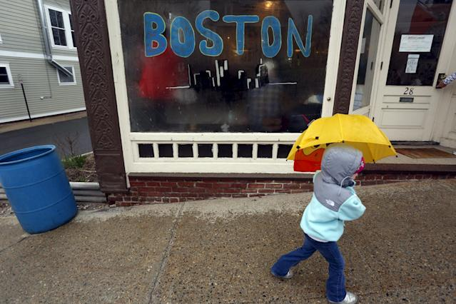 """A child with an umbrella passes by a window painted with """"Boston"""" near the Boston Marathon start line in Hopkinton, Massachusetts, April 20, 2015. A field of 30,000 runners is set to line up for the 119th running of the world's oldest annual marathon. REUTERS/Dominick Reuter"""