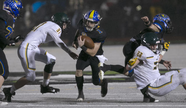 Sutter Union's Cory McIntyre, center, runs past Paradise's Josh Alvies, left, and Ashton Wagner, right, during the first quarter of a Northern Section Division III high school football playoff game in Yuba City, Calif., Saturday, Nov. 30, 2019. Paradise had an undefeated season and made it to the section championship game a year after the deadliest wildfire in California history that killed dozens and destroyed nearly 19,000 buildings including the homes of most of the players. (AP Photo/Rich Pedroncelli)