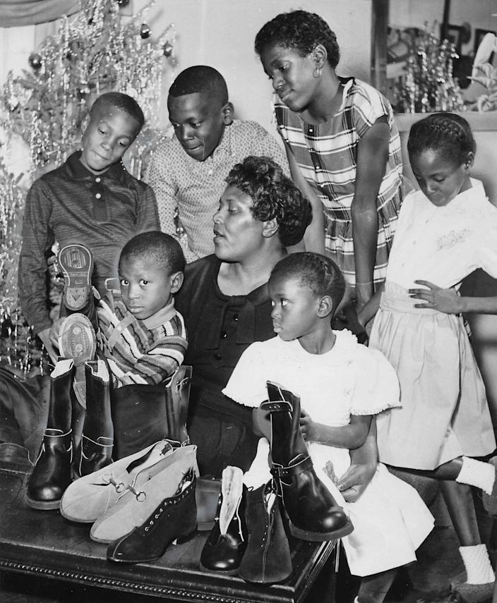 Helen Arnold and six of her children look over some of the Christmas gifts purchased with a $350 gift from an unknown benefactor in 1959. Clockwise from left, the children are Gerald, 6, Gary, 9, John, 11, Gale, 12, Carla, 7, and Donna, 4.
