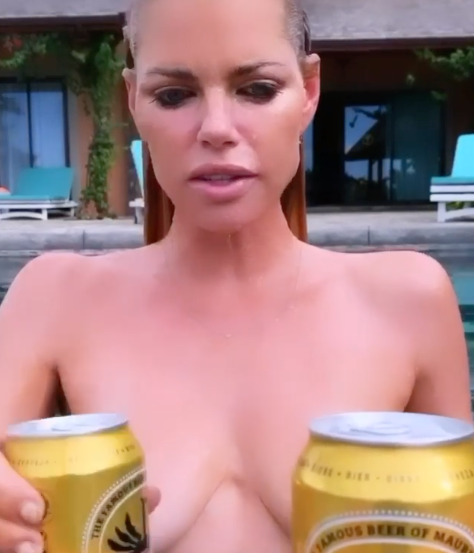 Sophie Monk nude with a pair of beers covering her chest.