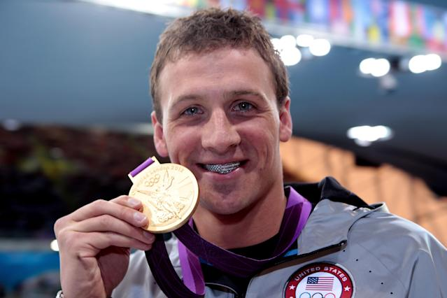 LONDON, ENGLAND - JULY 28: Ryan Lochte of the United States celebrates with his Gold Medal during the Medal Ceremony for the Men's 400m Individual Medley on Day 1 of the London 2012 Olympic Games at the Aquatics Centre on July 28, 2012 in London, England. (Photo by Adam Pretty/Getty Images)