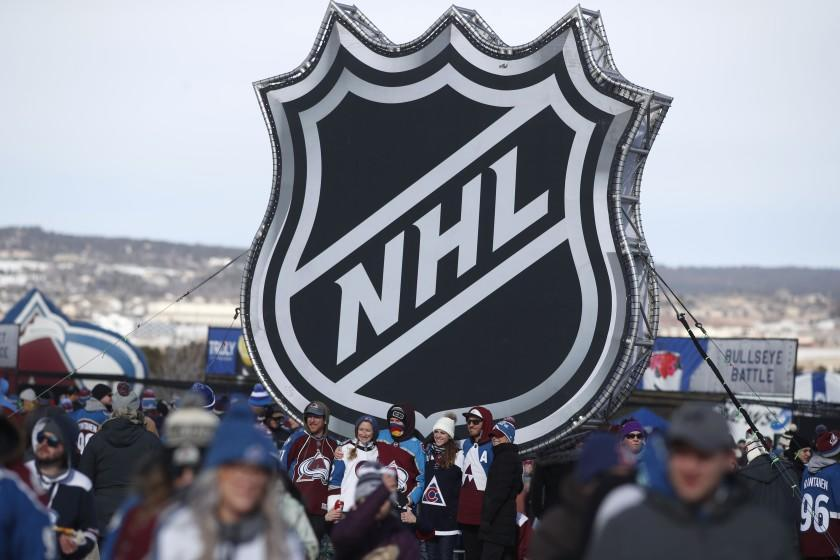"""In this Feb. 15 photo, fans pose below the NHL logo outside Falcon Stadium before an outdoor game between the Kings and Colorado Avalanche in Colorado Springs. <span class=""""copyright"""">(David Zalubowski / Associated Press)</span>"""