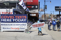 FILE - In this April 1, 2021, file photo, person stands with a sign related to COVID-19 testing as Chicago Cubs fans pass by outside of Wrigley Field on the opening day baseball game in Chicago. U.S. healthy officials say that most fully vaccinated Americans can skip testing for COVID-19, even if they were exposed to someone infected. (AP Photo/Shafkat Anowar, File)