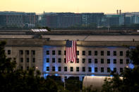 An American flag is unfurled at the Pentagon in Washington, Saturday, Sept. 11, 2021, at sunrise on the morning of the 20th anniversary of the terrorist attacks. The American flag is draped over the site of impact at the Pentagon. (AP Photo/J. Scott Applewhite)