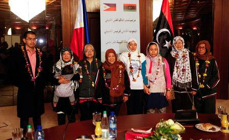 Filipino nurses, who were freed from Islamic State militants by Libyan forces in Sirte, pose for a group photo during a handover ceremony in the presence of a Filipino envoy in Tripoli, Libya, February 27, 2017.   REUTERS/Ismail Zitouny
