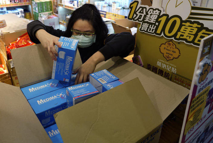 A saleswoman takes out face masks from a box as people queue up waiting to purchase face masks outside a shop in Hong Kong, Wednesday, Jan. 29, 2020. A viral outbreak that began in China has infected more than 6,000 people in the mainland and more than a dozen other countries. (AP Photo/Vincent Yu)