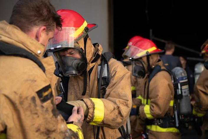 """Sailors help one another with their firefighting gear before boarding the amphibious assault ship Bonhomme Richard on Wednesday morning in San Diego. At least two sailors responding to the fire have since tested positive for the coronavirus. <span class=""""copyright"""">(Seaman Lily Gebauer/ U.S. Navy)</span>"""