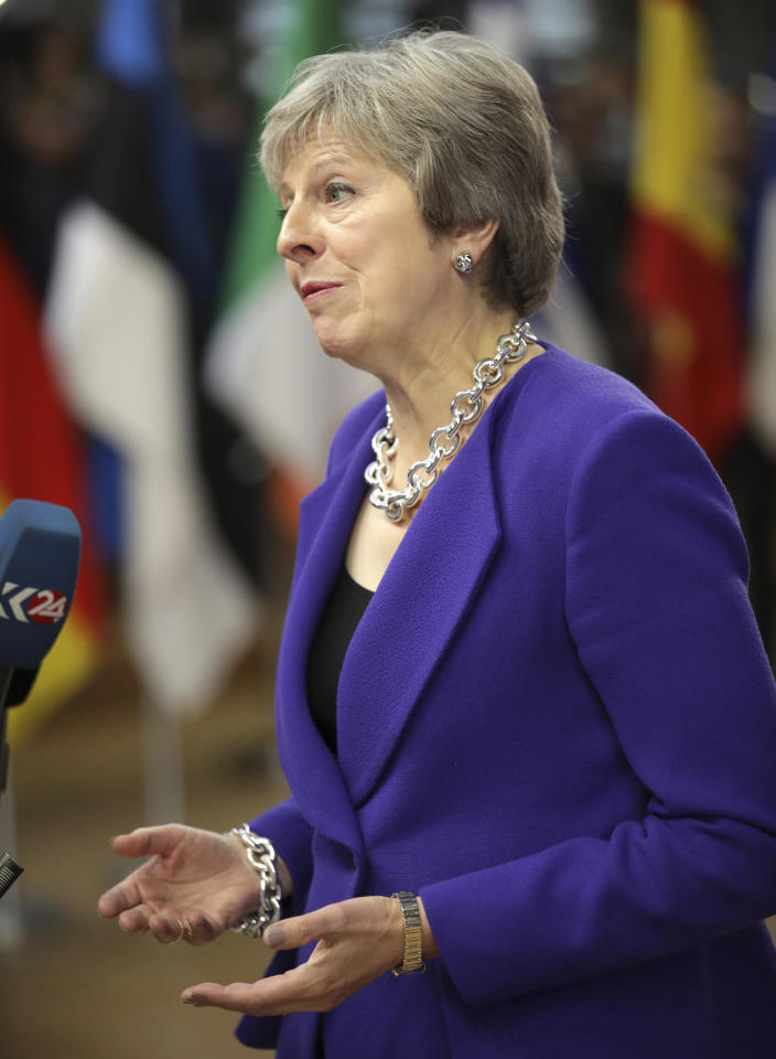 British Prime Minister Theresa May speaks with the media as she arrives for an EU summit at the Europa building in Brussels, Thursday, Oct. 18, 2018. EU leaders meet for a second day on Thursday to discuss migration, cybersecurity and to try and move ahead on stalled Brexit talks. (AP Photo/Olivier Matthys)
