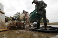 Residents Kazuo Saito, right, and Sumiko Saito clean up their home Monday, Oct. 14, 2019, in Kawagoe City, Japan. Typhoon Hagibis dropped record amounts of rain for a period in some spots, according to meteorological officials, causing more than 20 rivers to overflow. Some of the muddy waters in streets, fields and residential areas have subsided. But many places remained flooded, with homes and surrounding roads covered in mud and littered with broken wooden pieces and debris. (AP Photo/Eugene Hoshiko)