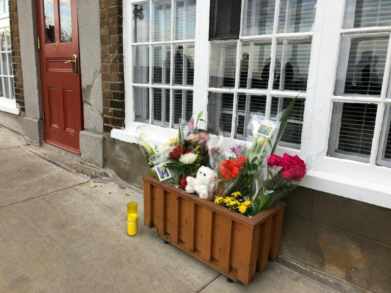 Flowers and a candle are placed in front of the house of a woman who died in a Halloween attack in Quebec City