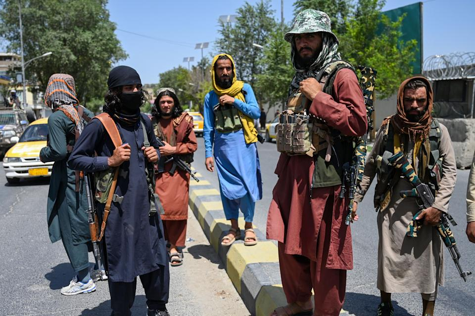 Taliban fighters stand guard along a street near Zanbaq Square in Kabul on August 16, 2021, after a stunningly swift end to Afghanistan's 20-year war, as thousands of people mobbed the city's airport trying to flee the group's feared hardline brand of Islamist rule. (Wakil Kohsar/AFP via Getty Images)