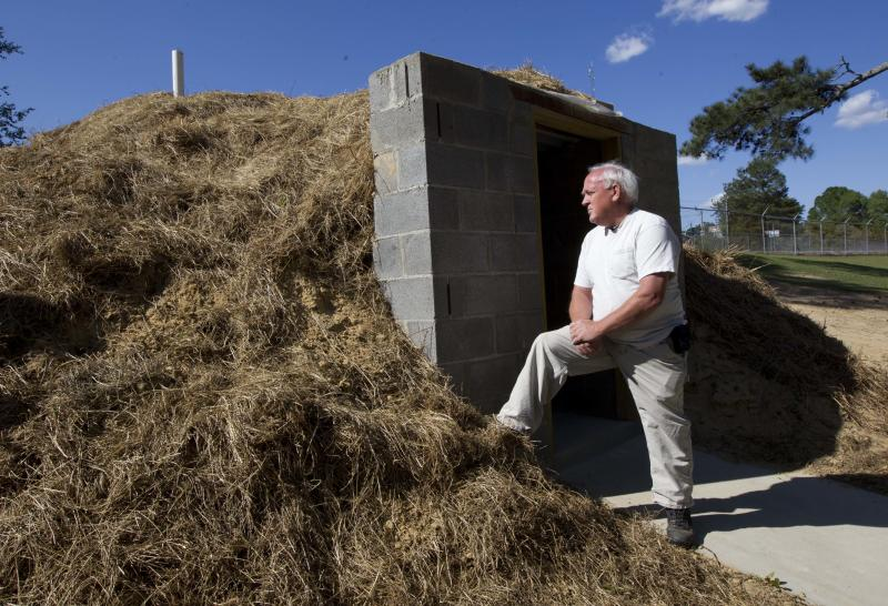 In this April 23, 2012, photo Freddie Wooten stands in front of the storm shelter he built at his own expense in Henager, Ala., following the 2011 tornado. When deadly twisters chewed through the Midwest and South in 2011, thousands of people in the killers' paths had nowhere to hide. Now many of those families are taking an unusual extra step to be ready next time: adding tornado shelters to their homes. (AP Photo/Dave Martin)