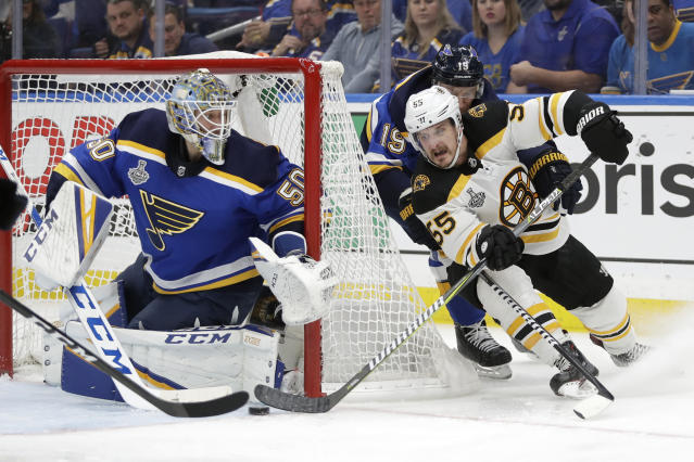 Boston Bruins center Noel Acciari (55) rounds the net against St. Louis Blues goaltender Jordan Binnington (50) during the third period of Game 6 of the NHL hockey Stanley Cup Final Sunday, June 9, 2019, in St. Louis. The Bruins won 5-1 to even the series 3-3. (AP Photo/Jeff Roberson)