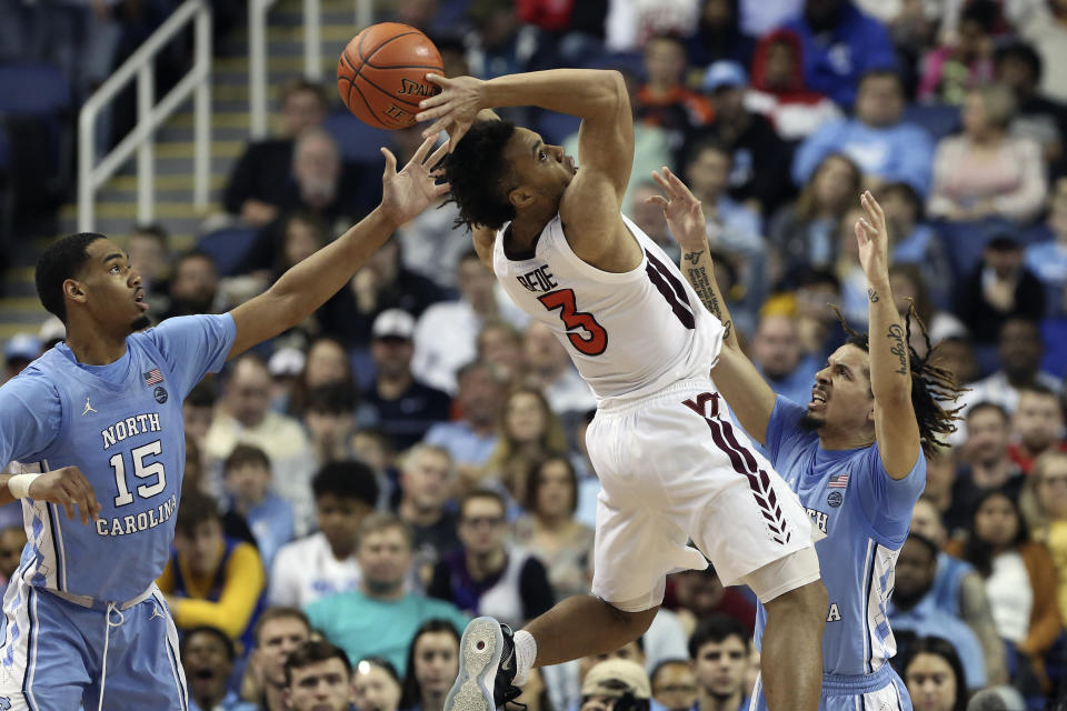 North Carolina forward Garrison Brooks (15) and guard Cole Anthony guard Virginia Tech guard Wabissa Bede (3) during the first half of an NCAA college basketball game at the Atlantic Coast Conference tournament in Greensboro, N.C., Tuesday, March 10, 2020. (AP Photo/Ben McKeown)