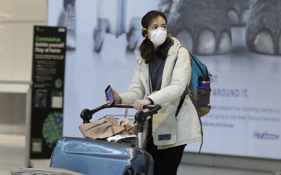 A woman wears a mask as she walks at Heathrow Airport Terminal 5, in London, Tuesday, March 24, 2020. Britain's Prime Minister Boris Johnson on Monday imposed its most draconian peacetime restrictions due to the spread of the coronavirus on businesses and social gatherings.  For most people, the new coronavirus causes only mild or moderate symptoms. For some it can cause more severe illness.(AP Photo/Kirsty Wigglesworth)