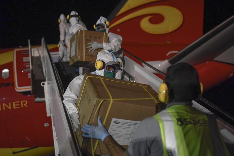FILE - In this March 30, 2020 file photo, Venezuelan workers, wearing protective face masks and suits as a preventive measure against the spread of the new coronavirus, unload humanitarian aid from China at the Simon Bolivar International Airport in La Guaira, Venezuela. China donated more than $215 million in supplies to allies in the region, and conducted clinical trials or plans to manufacture vaccines in five countries. (AP Photo/Matias Delacroix, File)
